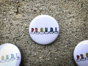 pinback button with PROUD in rainbow colors